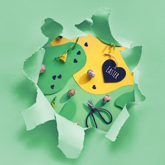 Paper hole showing easter background. flat lay, top view with quail eggs, scissors, heart, freesia flowers and black confetti.