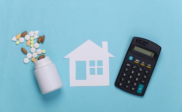 Бумажный домик, бутылочные таблетки и калькулятор на синем, концепция медицинского страхования