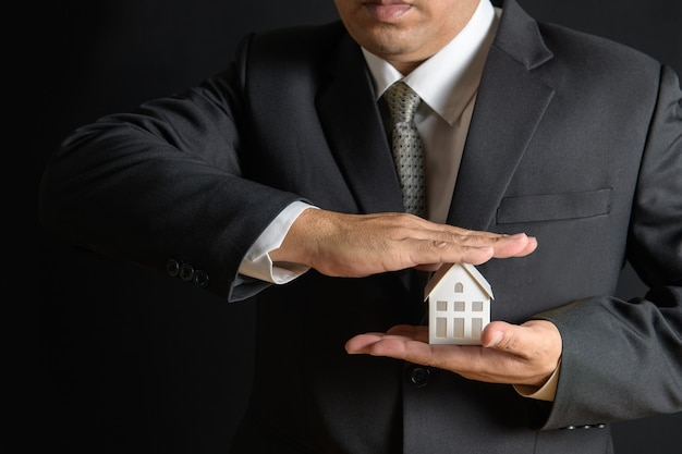 紙の家は、顧客、住宅購入者、保険、新しい所有者との準備ができて家を保護するために、不動産業者のビジネスマンの手で覆われています。住宅保険の販売コンセプト。