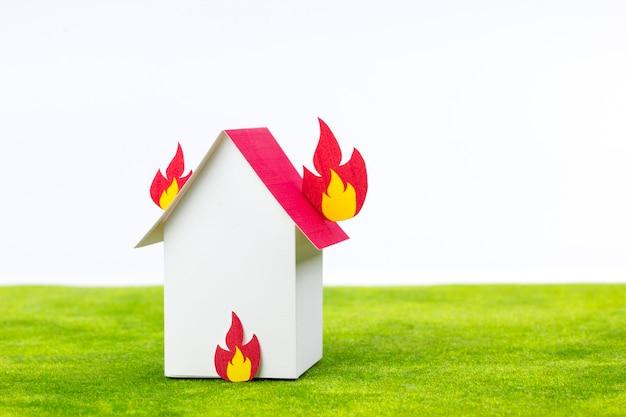 家に付いている燃えている火のある紙の家のモデル。