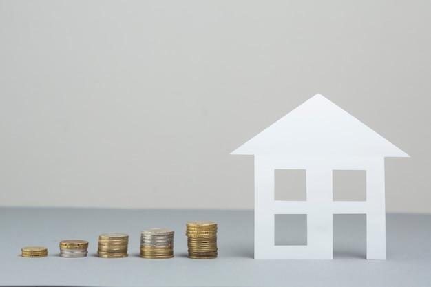 灰色の表面に増加するコインのスタックを持つ紙の家モデル