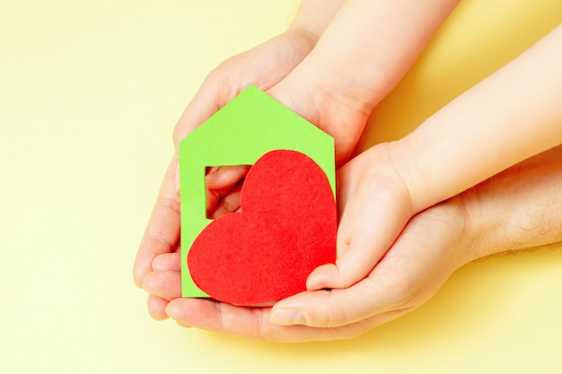Paper house with heart in hands