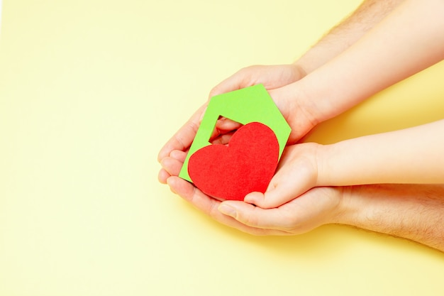 Paper house with heart in hands.