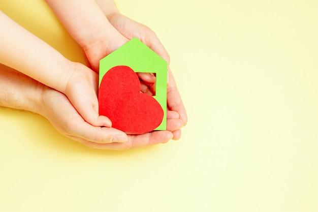 Бумажный домик с сердцем в руках.