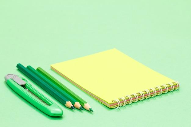 Нож для бумаги, цветные карандаши и тетрадь на зеленом фоне. снова в школу концепции. школьные принадлежности. малая глубина резкости.