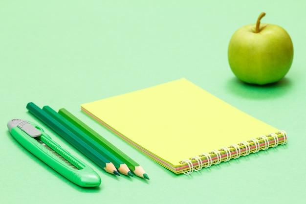 Нож для бумаги, цветные карандаши, блокнот и яблоко на зеленом фоне. снова в школу концепции. школьные принадлежности. малая глубина резкости.