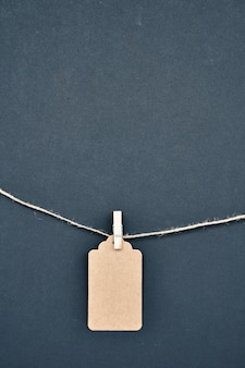 Paper labels are attached with clothespins to the rope on black.