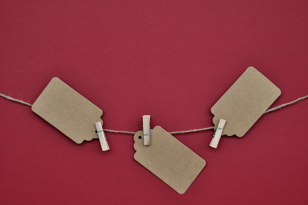 Paper labels are attached with clothespins to the rope on red.
