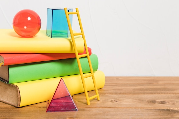 Paper ladder on stack of colorful books and toys