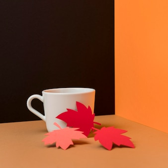 Paper leaves next to cup of coffee