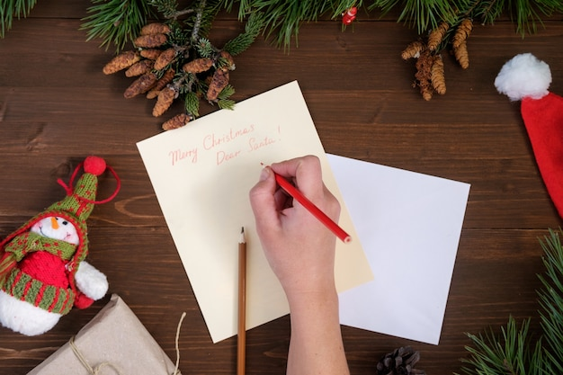 Paper letter to santa claus on a wooden table with toys, pine branches, fir cones pencils and