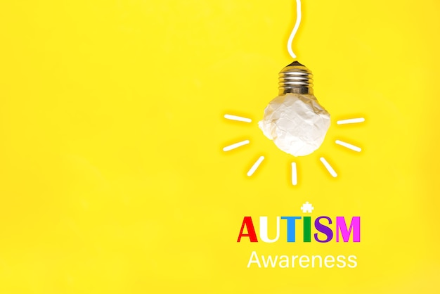 Paper light bulb on a yellow background, world autism awareness day