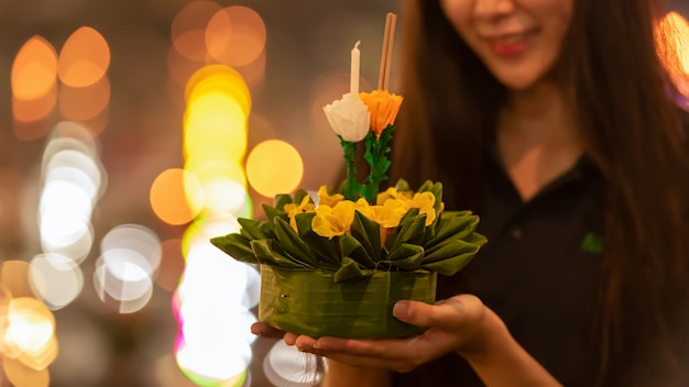 Paper lotus flower with candle floating on a river at night in loy krathong festival