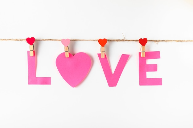 Paper love word on clothesline isolated on white. pink paper for notes on the clothespin with hearts