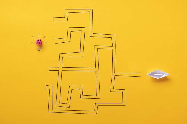 Лодка-оригами из бумаги пытается пройти через лабиринт к лампочке в концептуальном образе идеи, усилий и исследований.
