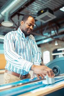 製紙。紙の製造で一生懸命働いている縞模様のシャツを着ている浅黒い肌の男