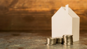 Paper miniature house with stack of coins on floor against wooden backdrop
