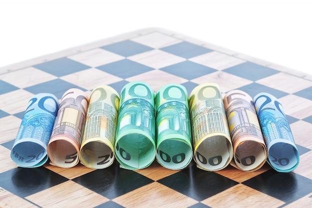 チェス盤にユーロの形で紙幣。コンセプトイメージ。
