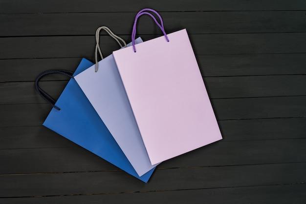 Бумажные разноцветные сумки для покупок на черном дереве