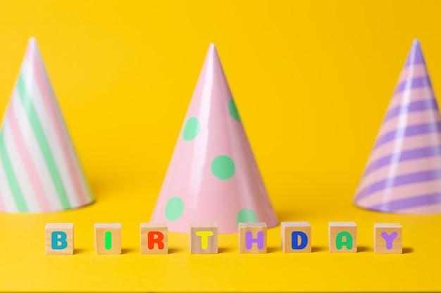 紙の色とりどりのホリデーキャップ。テキストの誕生日と木製の立方体。パーティーと誕生日のコンセプト。