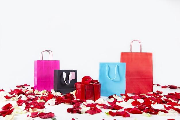 Бумажные разноцветные хозяйственные сумки и подарочная коробка с лепестками на день святого валентина подарки. праздничные покупки.