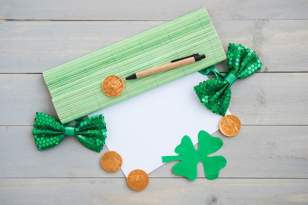 Paper near clovers, coins, bow ties and bamboo mat