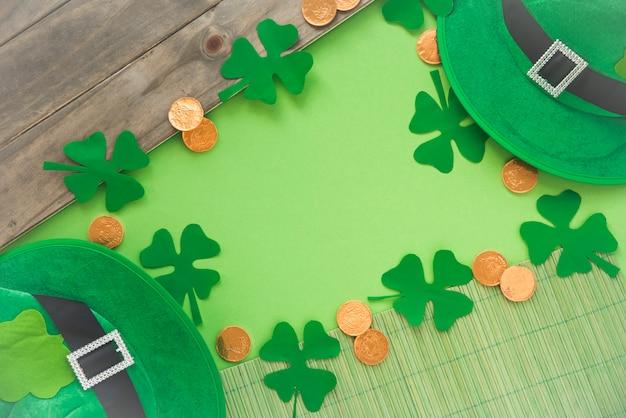 Paper near coins, decorative clovers and saint patricks hat