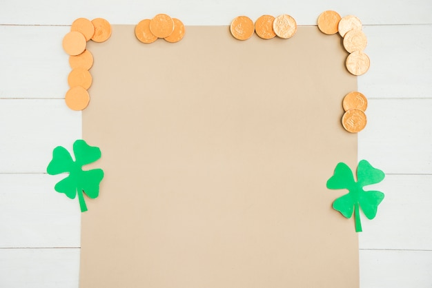 Paper near coins and decorative clovers