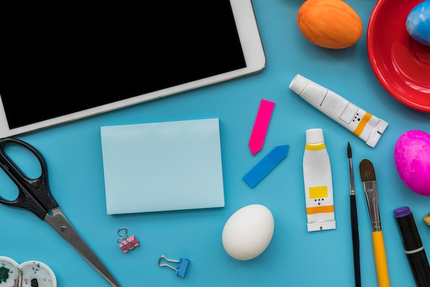 Paper near easter eggs, tablet and stationery