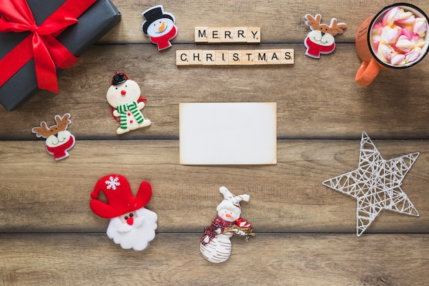 Paper near merry christmas title, present box and decorative toys