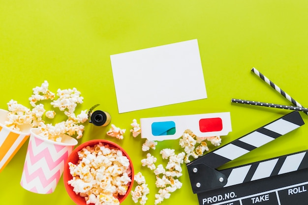 Paper near popcorn, clapboard and 3d glasses