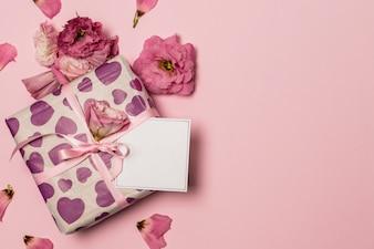 Бумага рядом с подарком и цветы и лепестки