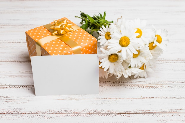 Paper near present box and bunch of flowers