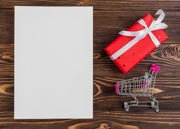 Paper near red present box with white ribbon and shopping trolley