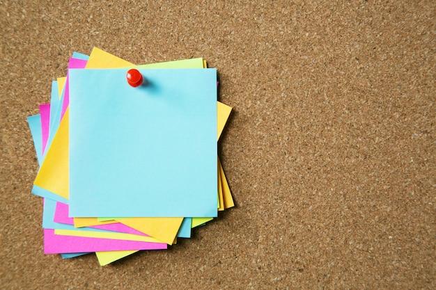 코르크 게시판에 종이 노트 패드 노란색 알림 스티커 메모 핀. 텍스트를위한 빈 공간입니다.
