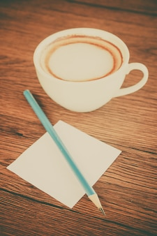 Paper note with pencil and coffee cup