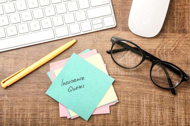 Бумажная записка с текстом цитаты страхования и клавиатурой на деревянном