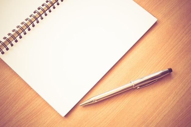 紙のノートブックとペン、フィルター効果のあるテーブルにレトロなヴィンテージスタイル