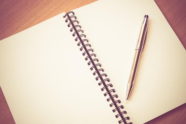 Бумажный блокнот и ручка на столе с эффектом фильтра ретро винтажный стиль