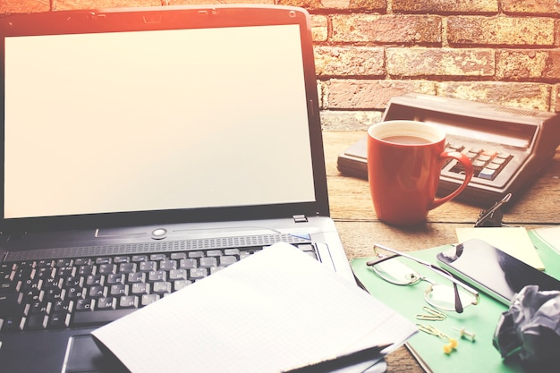 Paper on notebook, cup of coffee and calculator on wooden