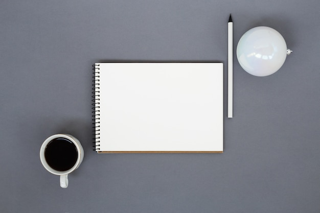 Бумажный блокнот, чашка кофе, карандаш и елочный шар