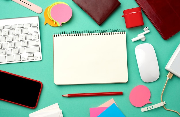 紙のノート、キーボード、ケーブル付き電源銀行、空白の黒い空の画面を持つ赤いスマートフォン