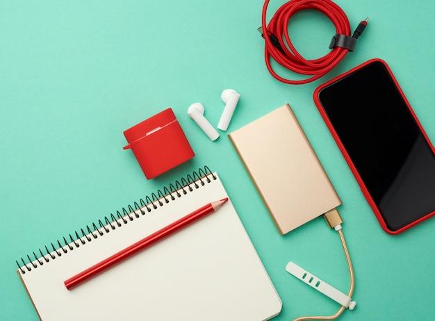 紙のノートブック、ケーブル付きのパワーバンク、空白の黒い空の画面とイヤーポッド付きの赤いスマートフォン