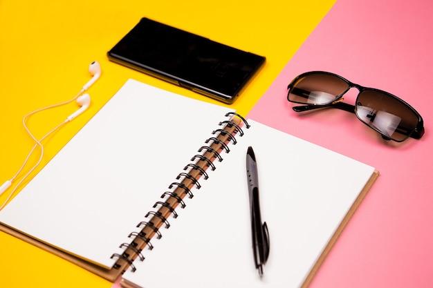 Бумажный блокнот, смартфон, солнцезащитные очки и держатель для визиток на двухцветном фоне