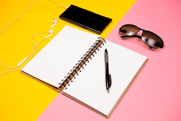 Paper notebook, smartphone, sunglasses and holder for business cards on two colored background