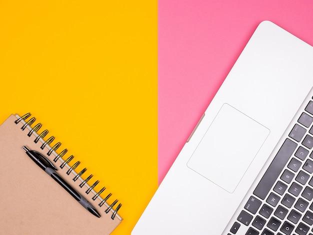 두 가지 색상의 배경에 노트북 옆에 펜이 있는 종이 노트북. 파스텔 색상입니다. 평면도 평면도