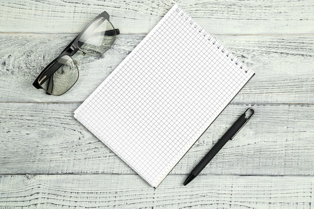Paper notebook with ballpoint pen and optical glasses on wooden isolated background