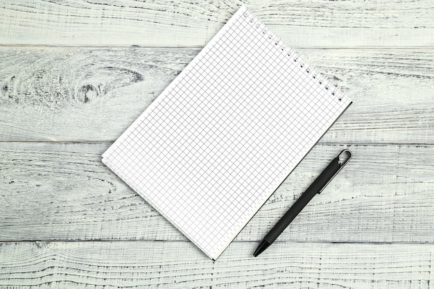 Paper notebook with ballpoint pen on wooden isolated background