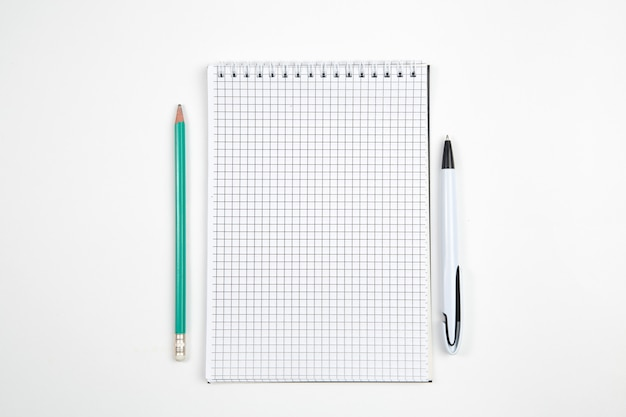 Paper notebook with pen or pencil on white isolated background. top view. flat lay . mockup