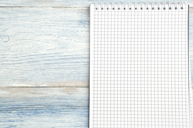 Paper notebook with space for text on a light blue old wooden background.